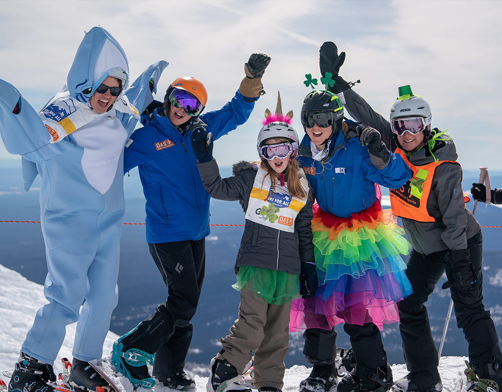 5 gals in shark costume, OAS jackets, tutus, unicorn horns and leprauchaun hats with hands in the air celebrating on mt bachelor summit