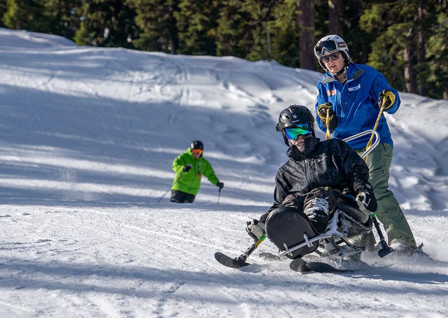 veteran skier in biski tethered by instructor