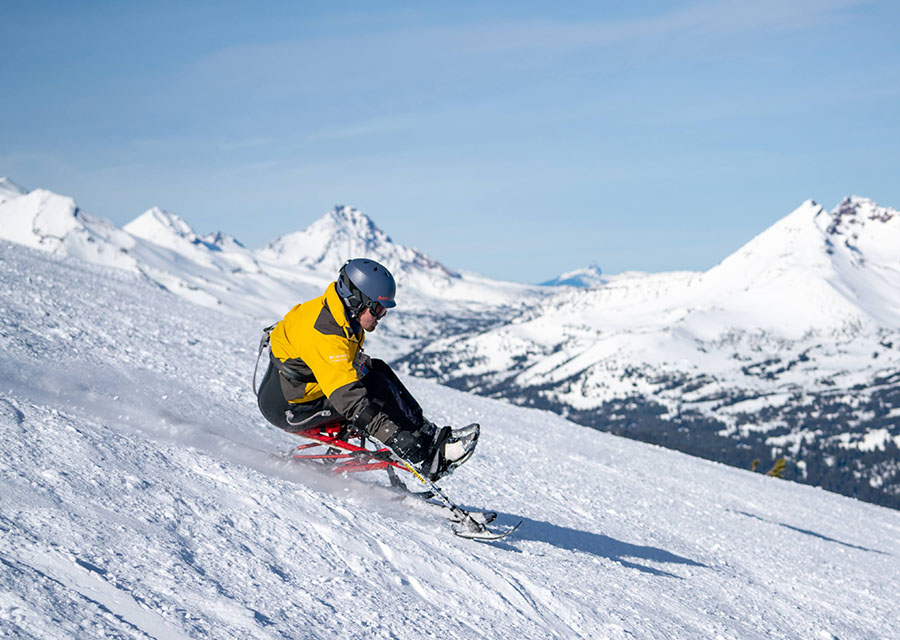 mono skier with mountains in background