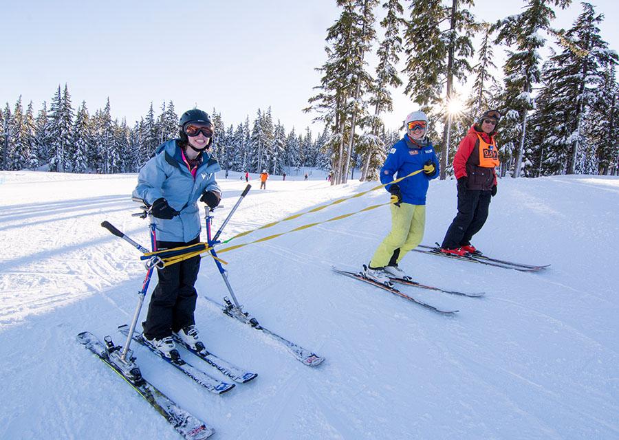 skiier sking on snow slider (walker on skis) with instructor and volunteer