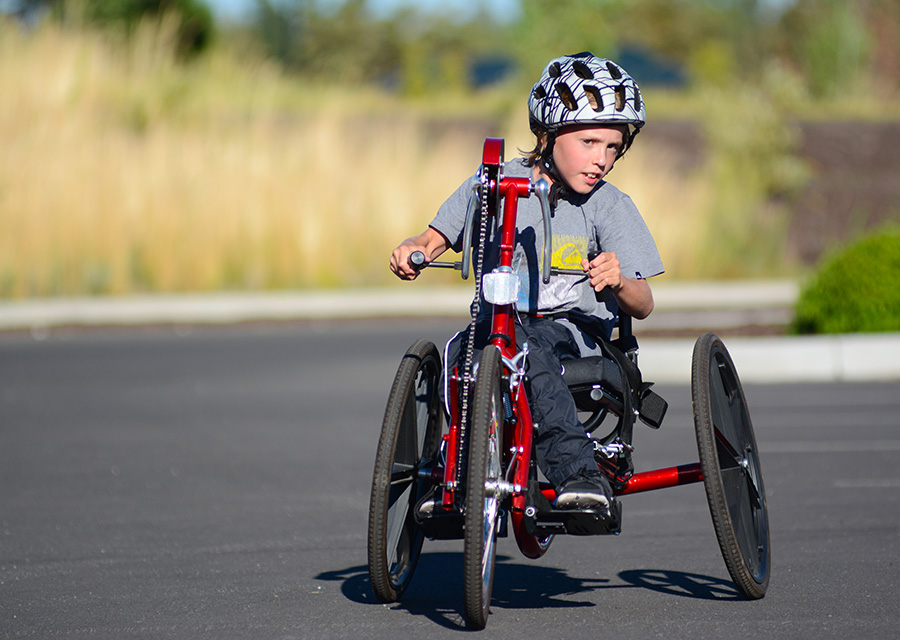 youth riding a handcycle