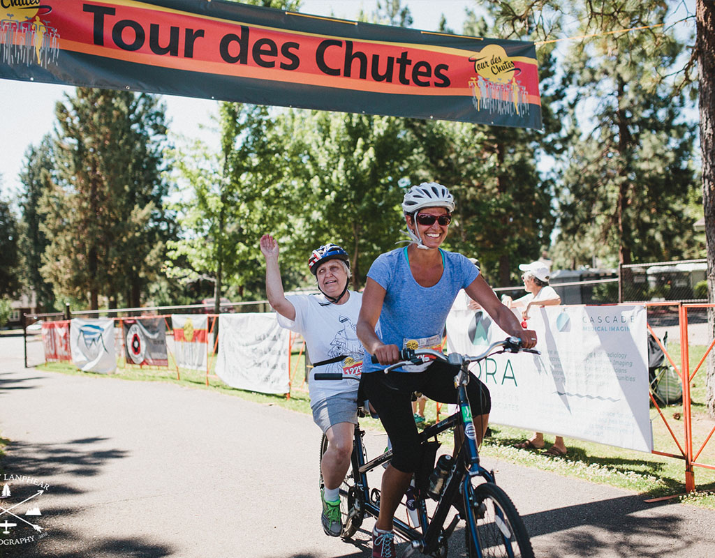 cyclist on tandem cycle at finish line of tour des chutes
