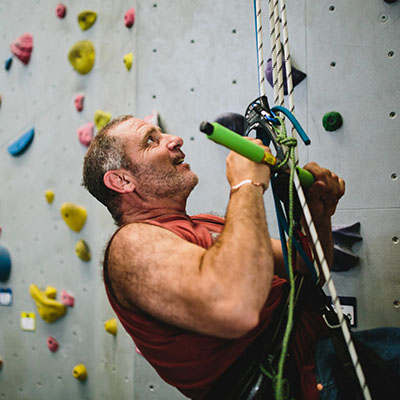 climber using wellman pulley system and pull up bar to climb in rock gym