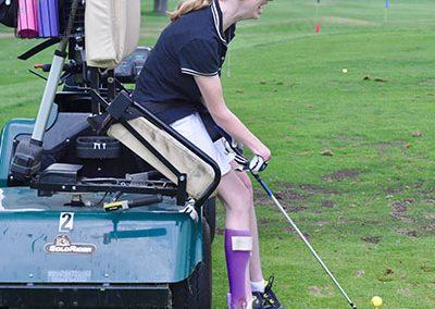 athlete hitting golf ball from solo rider adaptive golf cart