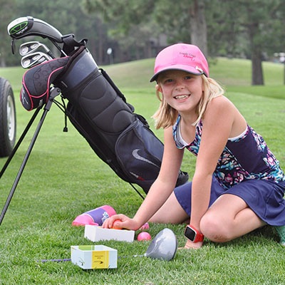 girl kneeling arranging golf balls with clubs in the background