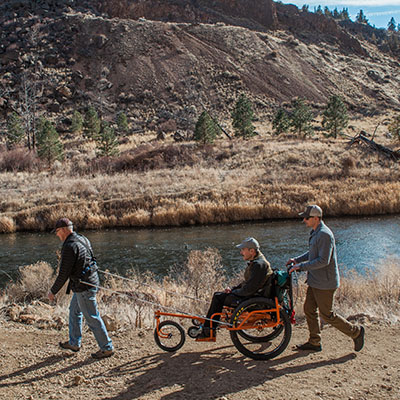 hiking wheelchair with one support person pulling and one person pushing