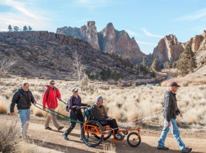group of people including one using a specialized wheelchair hiking at Smith Rock State Park