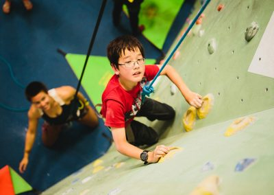 youth rock climbing in a climbing gym