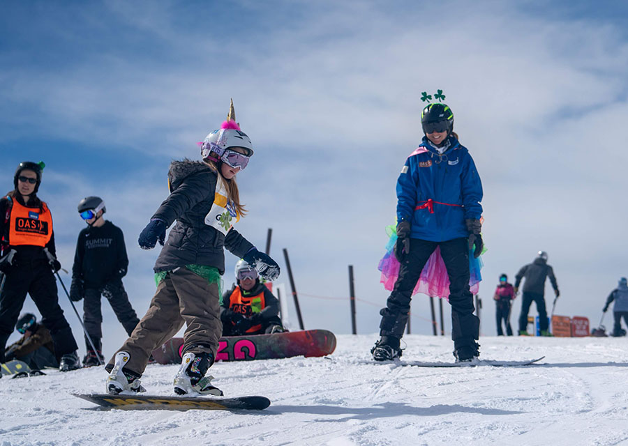 girl with unicorn horn on helmet snowboarding with instructor in costume coaching from uphill