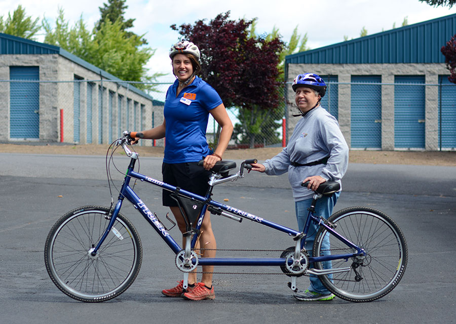 oas staff and participant with tandem bike in OAs office parking lot