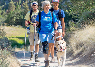 female hiker who is blind hiking with her guide dogs and two guides