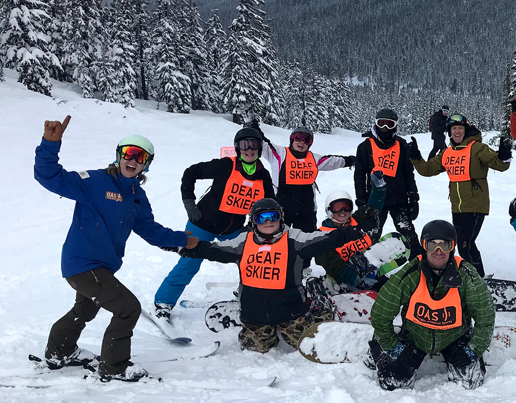 "group of deaf skiers signing ""PAH!"" which means at last in asl"
