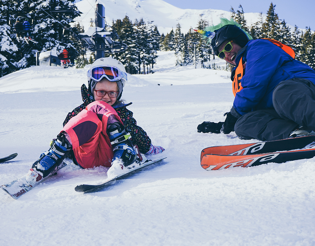 young girl skier sitting down on the snow giggling with OAS instructor wearing unicorn laying on snow next to her smiling