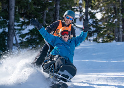woman in sit ski with arms in the air in excitement being bucket assisted by OAS instructor
