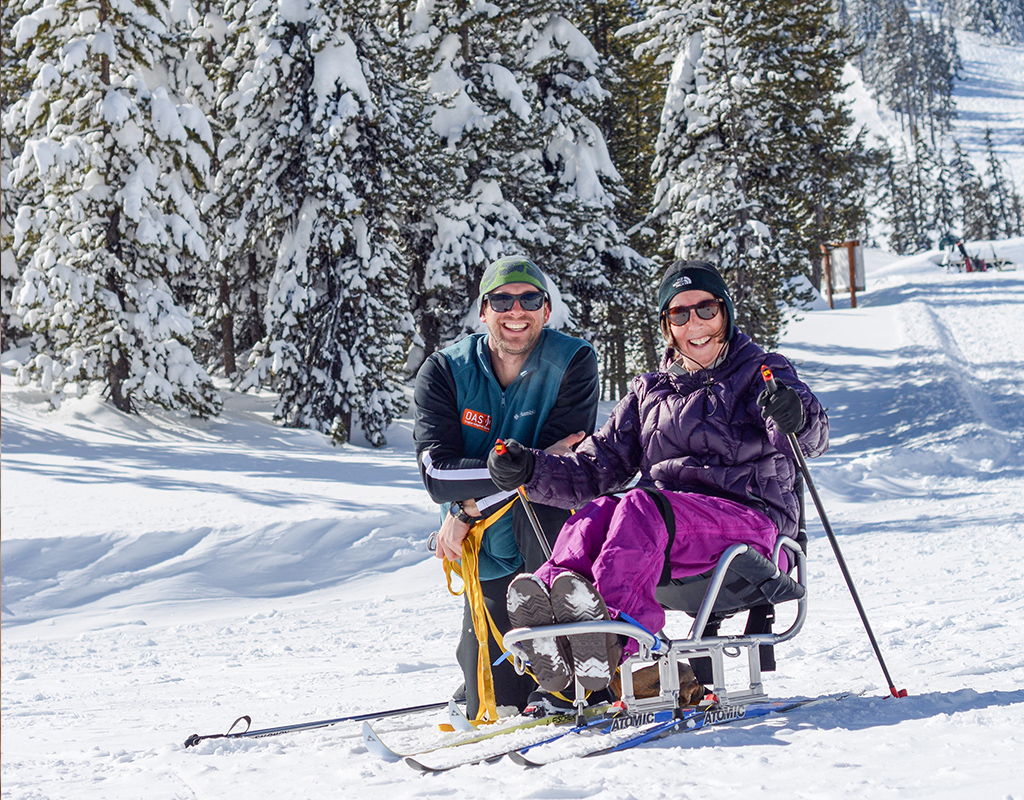 nordic sit skier with OAS instructor posing in beautiful sunny snowy landscape