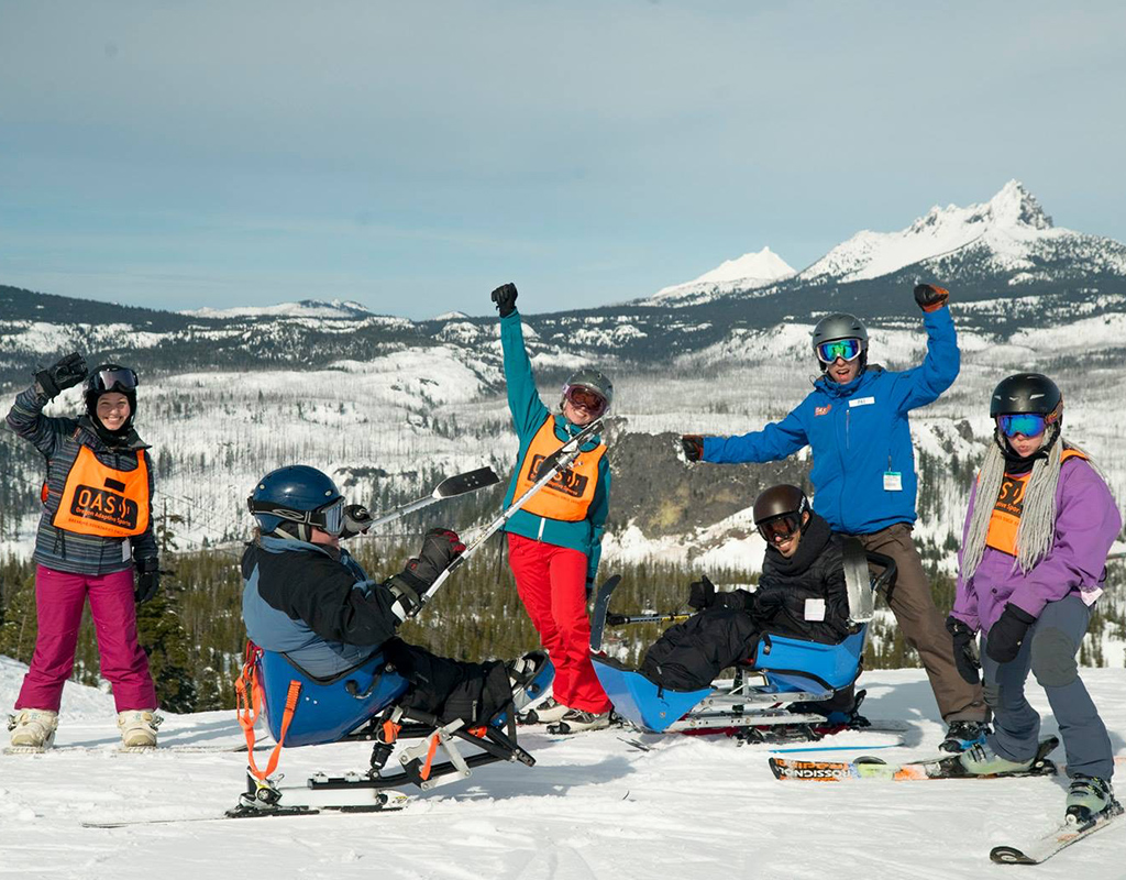 group of skiers with arms and outriggers in the air with excitement and three finger jack in the background