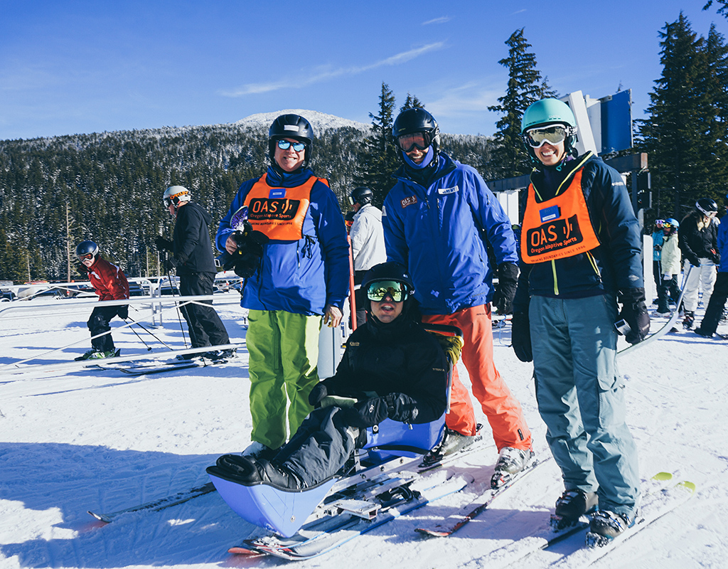 group including OAS sit skier, instructor and volunteers at base of ski lift with tumalo mountain in the background