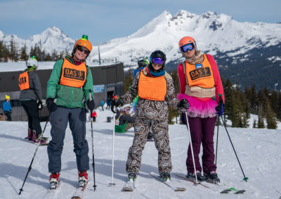 three skiers on the mountain on a beautiful bluebird ski day