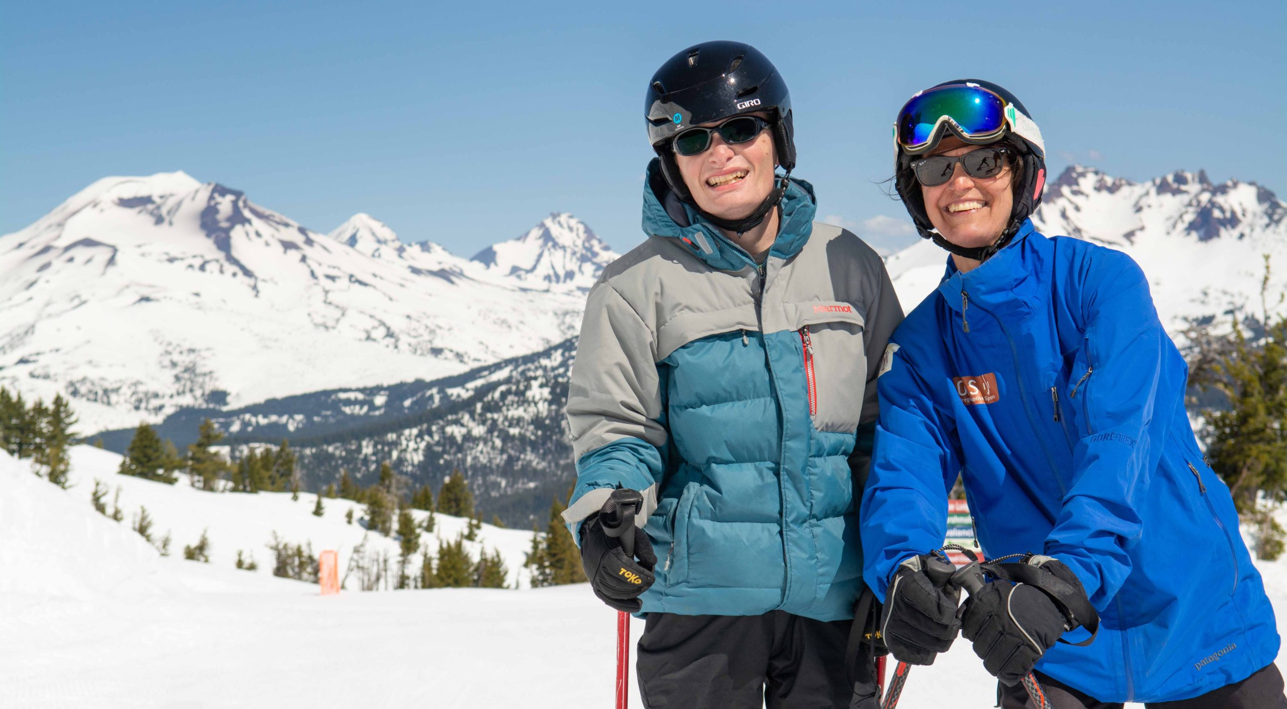 OAS skier and instructor smiling on a sunny day at Mt Bachelor