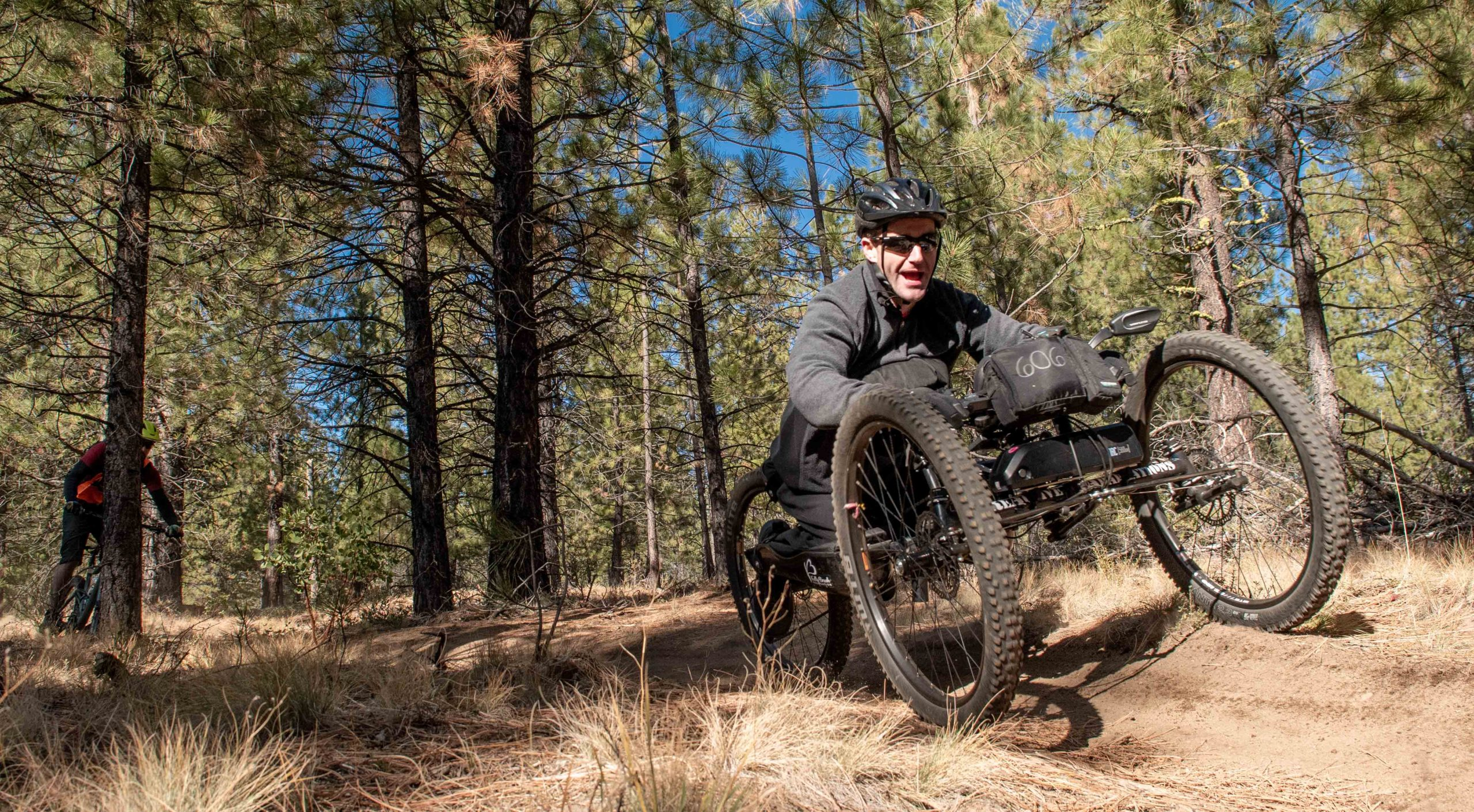 off road handcyclist smiling and riding on a trail