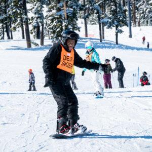 oas athlete in deaf skier bib snowboarding down hill