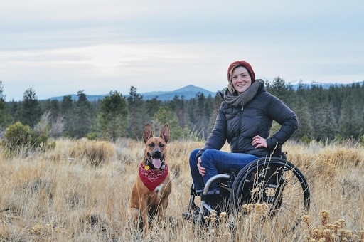 ashley schahfer with her dog sam in a meadow in front of the mountains