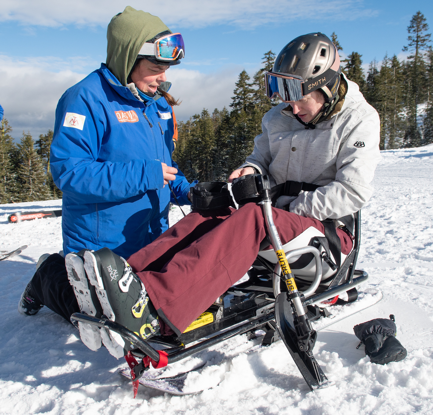 sit skier buckling herself into the bi ski with instructor lisa at her side