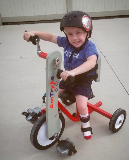 kid on hand and foot powered therapeutic bike