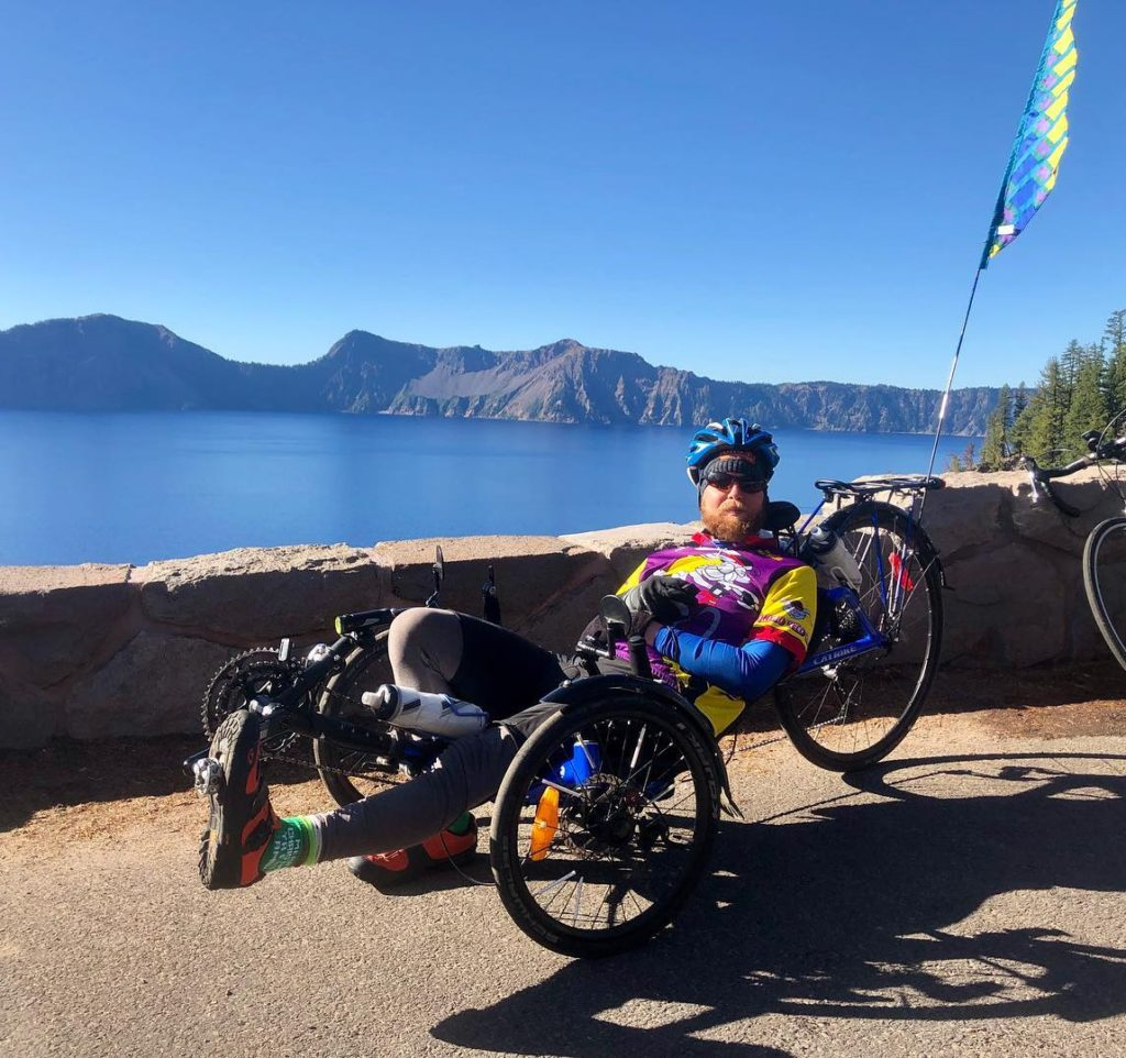 cyclist on recumbent bike in front of crater lake