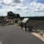 paved path surrounded by lava with info sign about land