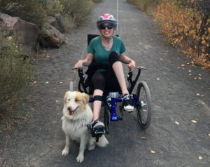 jana smiling on recumbent bike on gravel trail with dog at her side