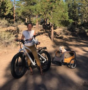 kellie on electric fat bike with dog in dog trailer