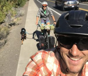 kellie on her bike with dog on a hip belt and partner taking the selfie of them