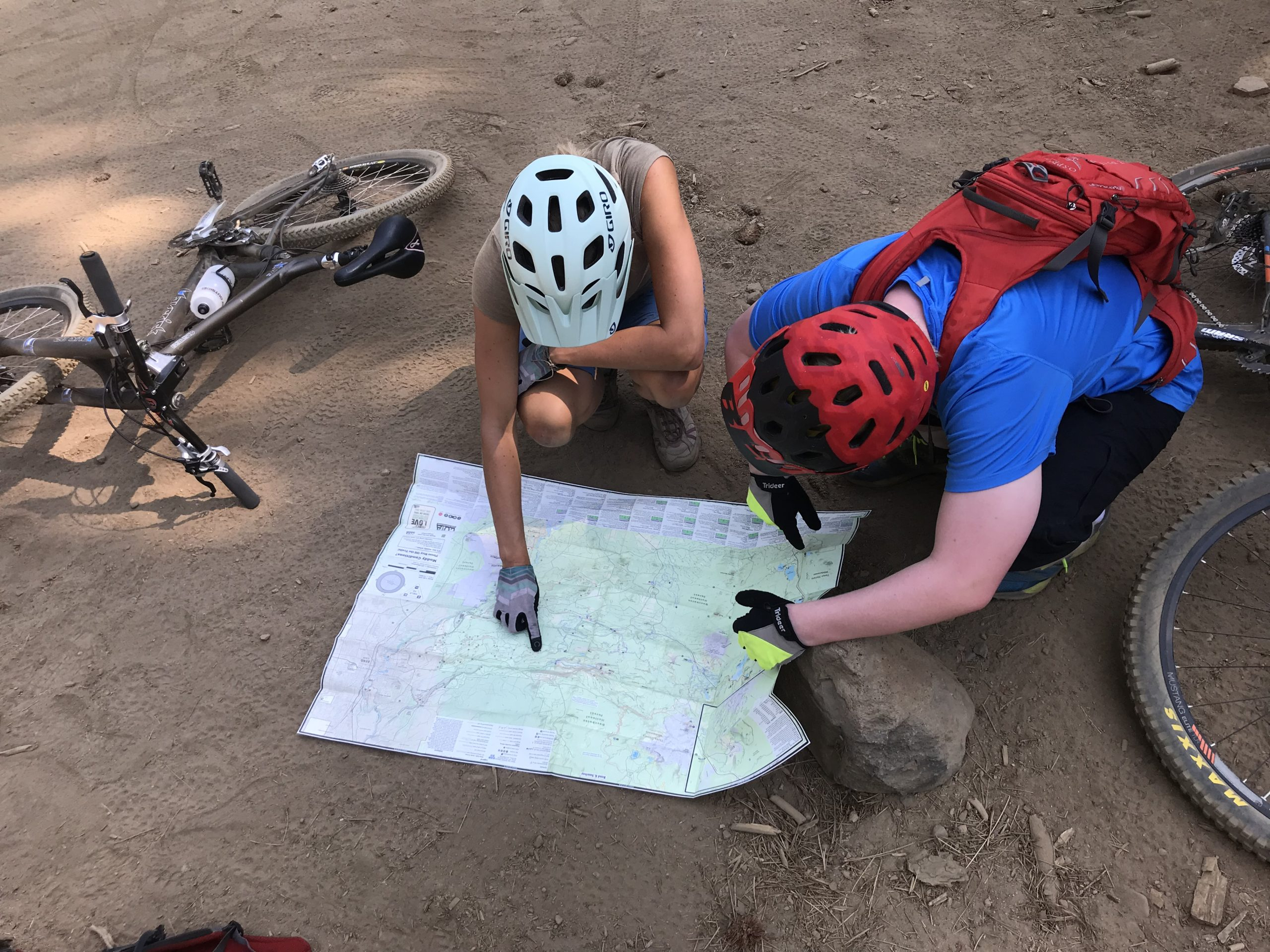 two cyclists with a map on the floor pointing to different points