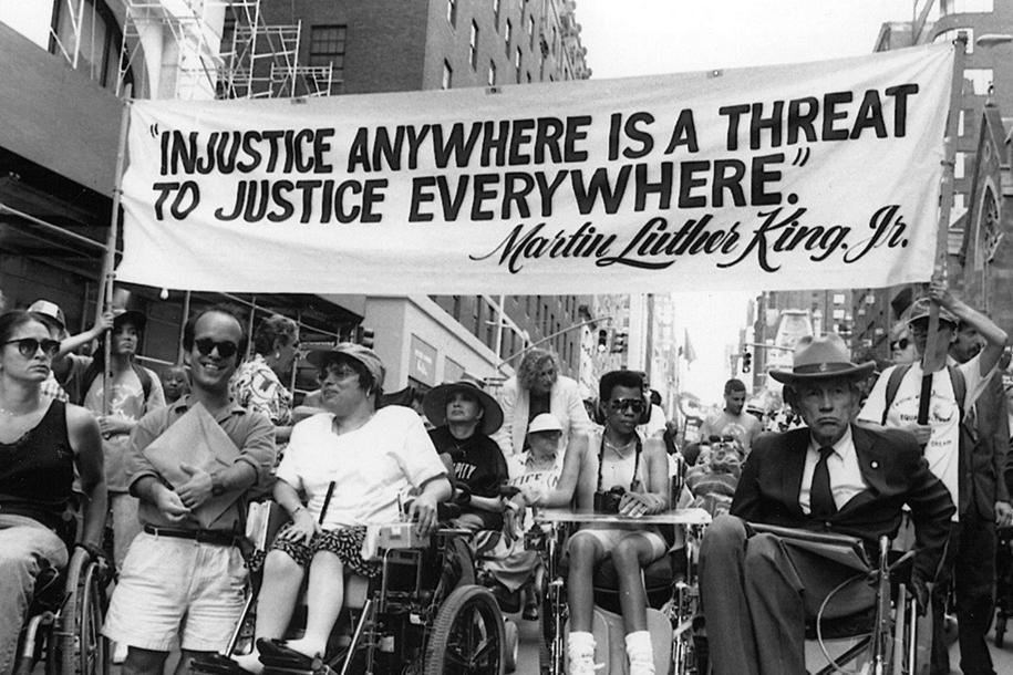 group of individuals with disabilities protesting with a sign that quotes from Martin Luther King - Injustice Anywhere is a Threat to Justice Everywhere