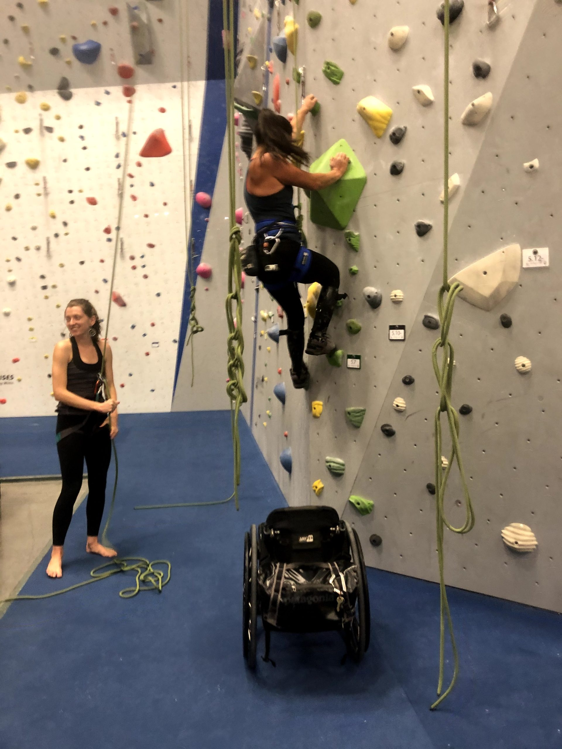 female athlete climbs up out of her wheelchair onto the wall of the rock gym while being belayed by female climber