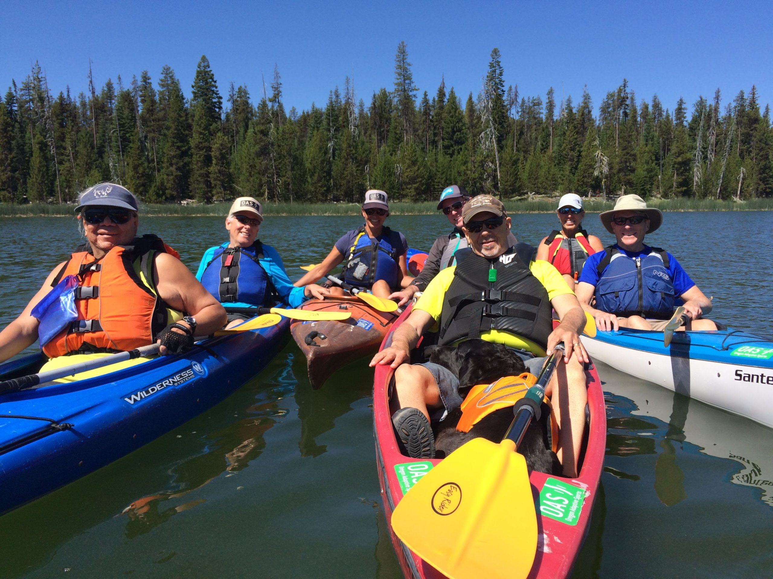 group of folks in kayaks on sparks lake grouped together holding onto each other's boats and smiling for photo