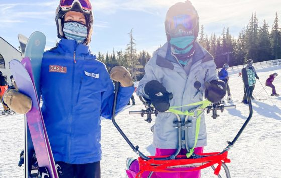 two skiers, one standing behind an adaptive ski frame
