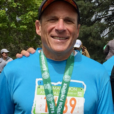 Bruce wearing a finishers medal for the 2016 Bend Half Marathon