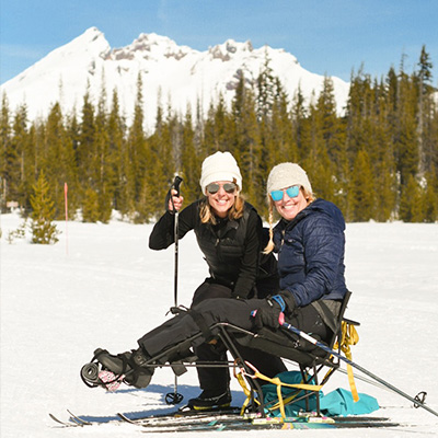 colleen in nordic sit ski with friend in front of mt bachelor