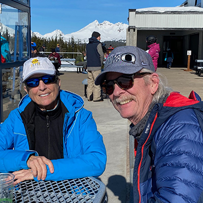 Scott Taylor and wife Lynne, sitting outside, snow capped mountains in background