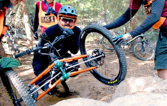 adaptive mountain biker supported by volunteers