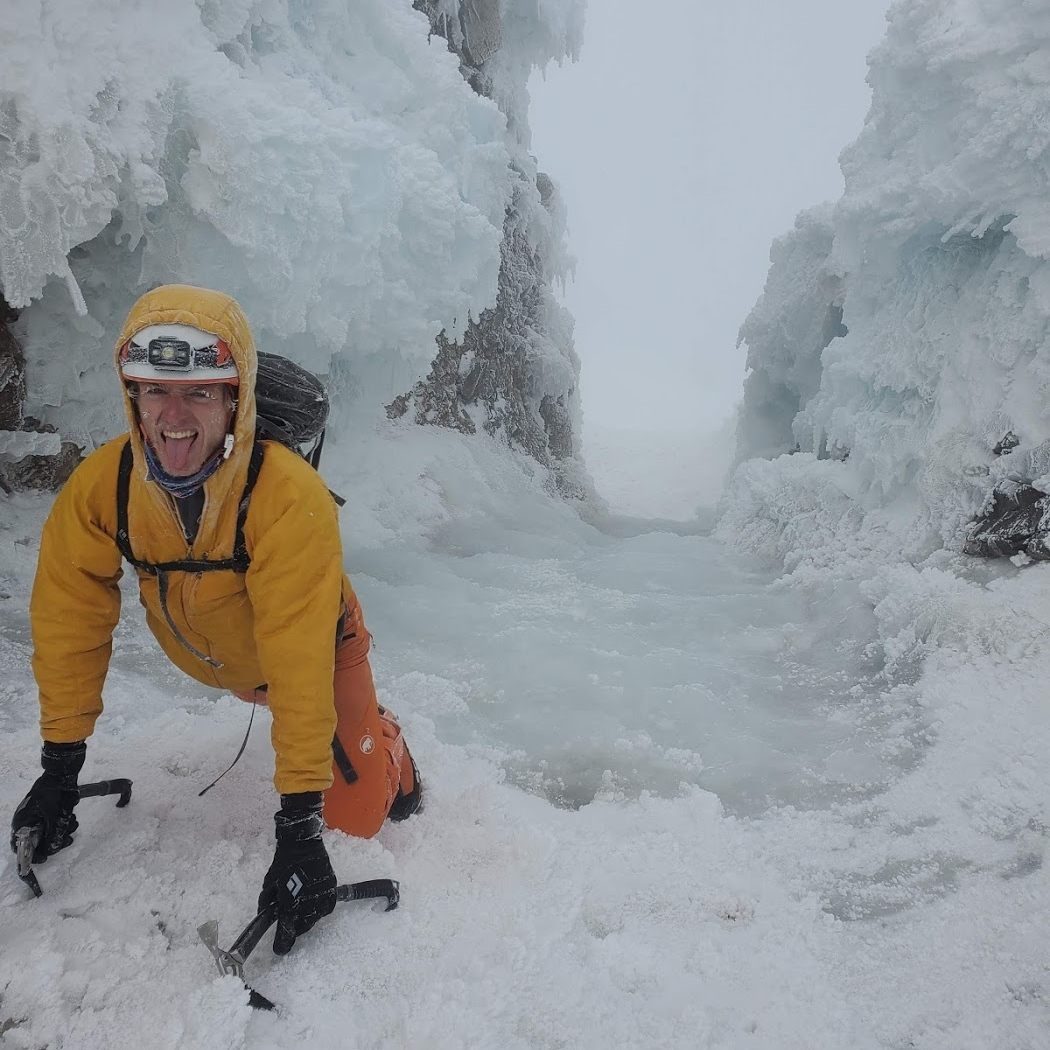 A person ice climbing up an icy chute