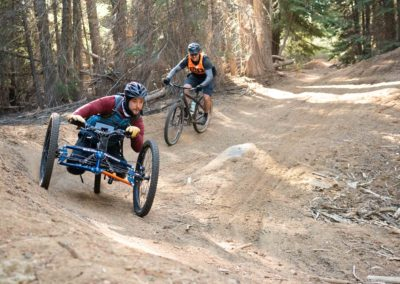 athlete riding an off road handcycle on a dirt trail